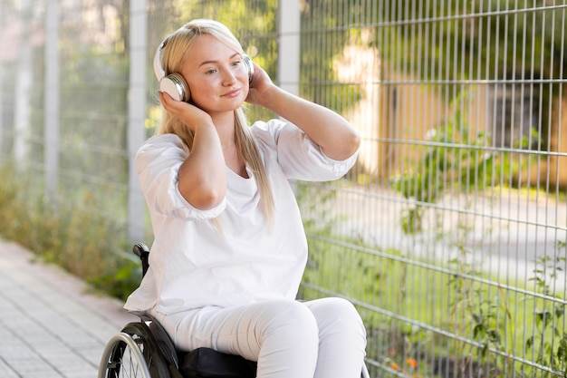 Donna sorridente in sedia a rotelle con le cuffie Foto Gratuite