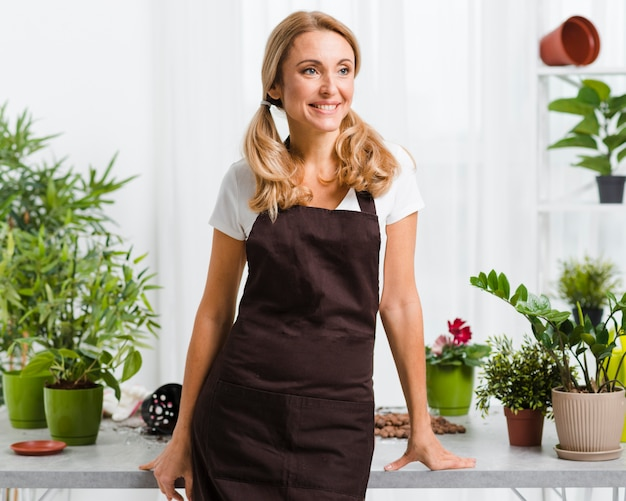 Smiley woman with apron in greenhouse Free Photo