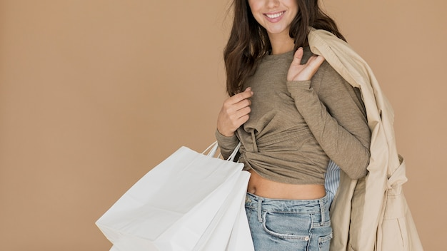 Smiley woman with coat on shoulder and shopping bags Free Photo