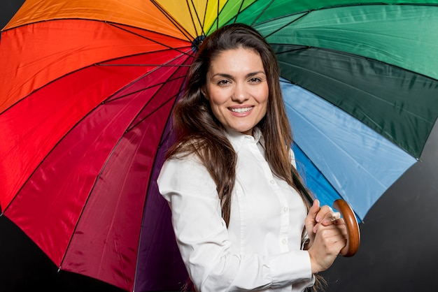 Smiley woman with colorful umbrella opened Free Photo