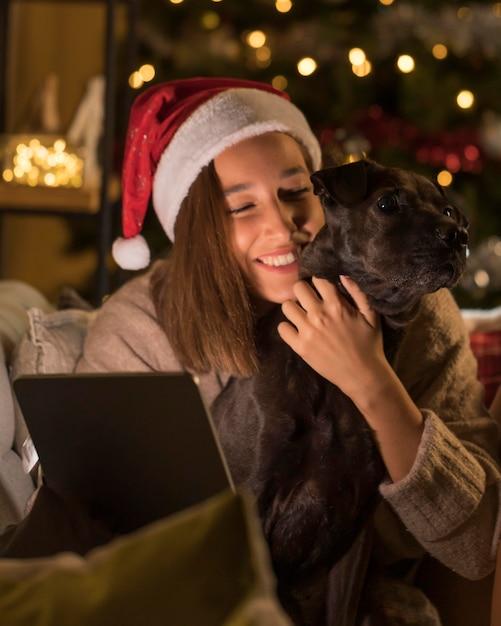 タブレットを保持している犬とサンタの帽子とスマイリーの女性 無料写真