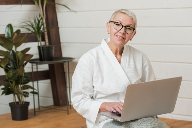 Smiley woman with glasses holding a laptop Free Photo