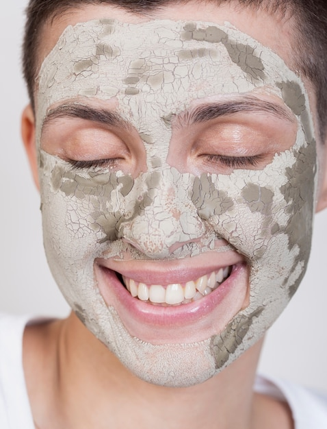Smiley woman with mud treatment on face Free Photo