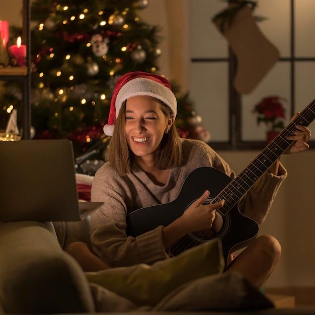 Donna di smiley con il cappello della santa che gioca chitarra davanti al computer portatile Foto Gratuite