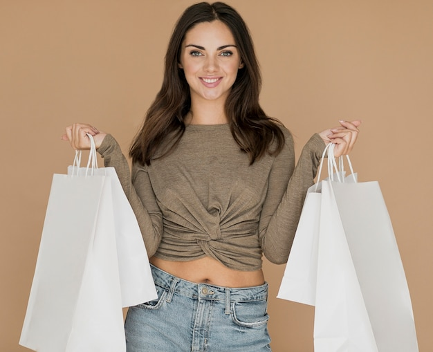 Smiley woman with shopping bags in both hands Free Photo