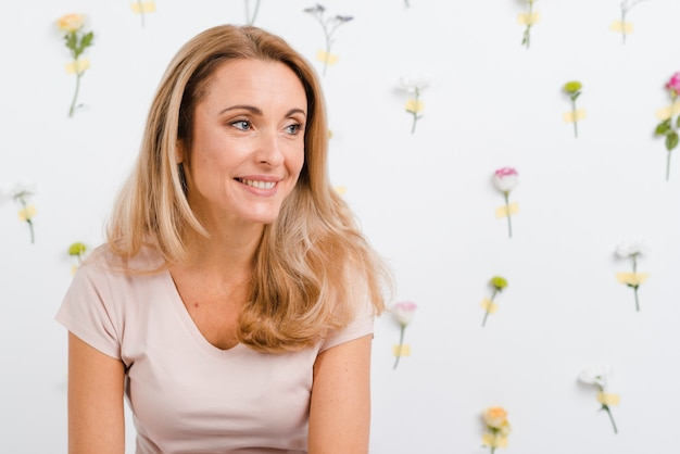 Smiley woman with spring flowers wall behind Free Photo