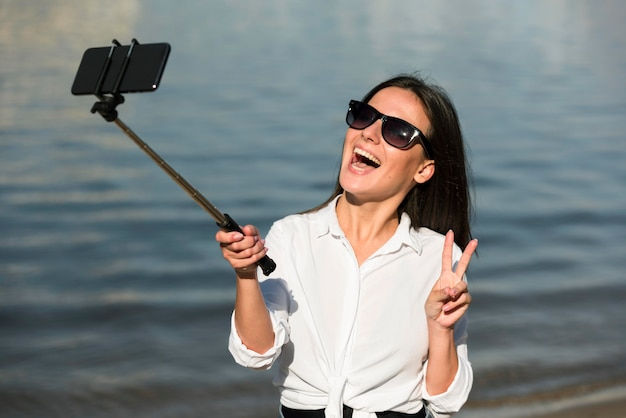 Улыбающаяся женщина в солнцезащитных очках, делающая селфи на пляже и делающая знак мира Бесплатные Фотографии