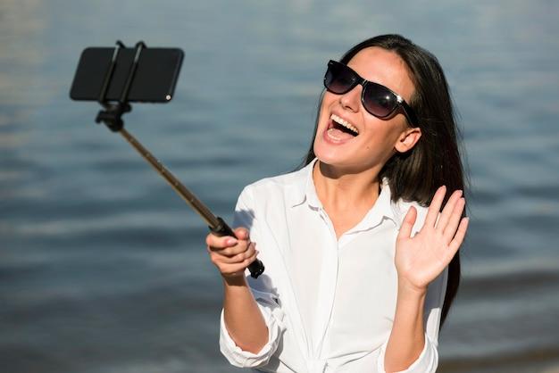 Смайлик женщина в солнцезащитных очках, делающая селфи на пляже Бесплатные Фотографии