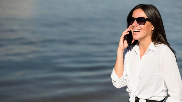 Смайлик женщина в солнцезащитных очках разговаривает по телефону на пляже Бесплатные Фотографии