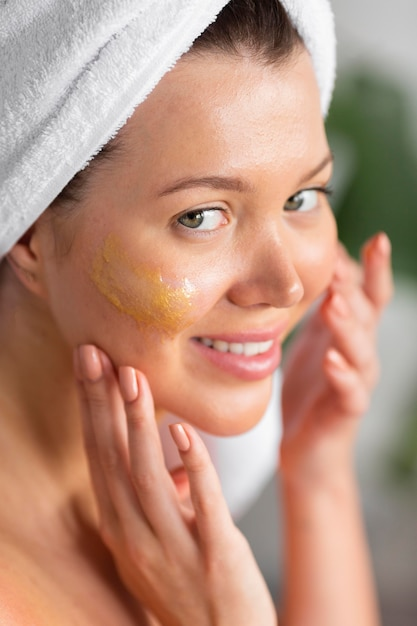 Smiley woman with towel on head applying skincare Premium Photo