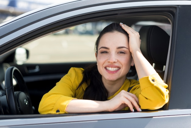 Smiley woman in yellow shirt sitting in the car Free Photo
