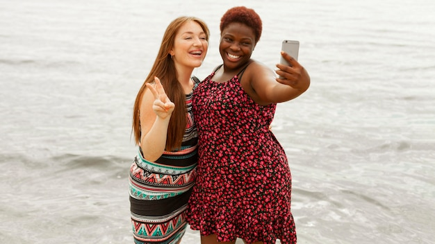 Smiley women at the beach taking selfie Free Photo