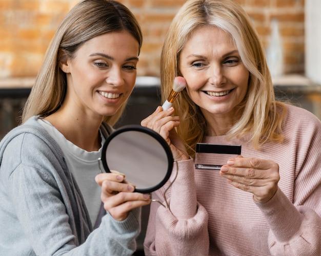 自宅で化粧をしているスマイリー女性 無料写真