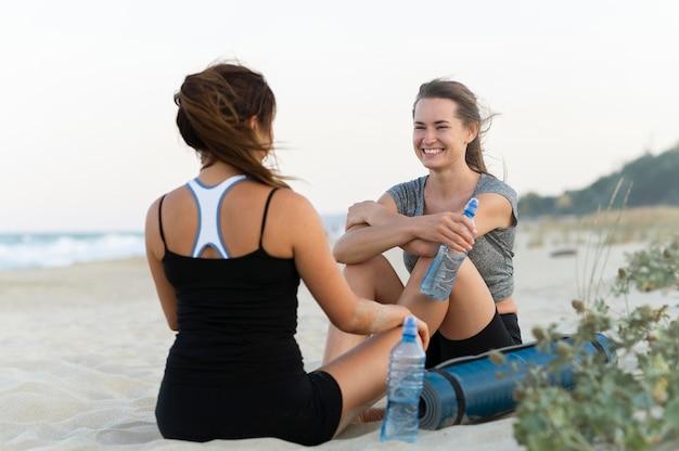 運動しながらビーチで休んでいるスマイリー女性 無料写真