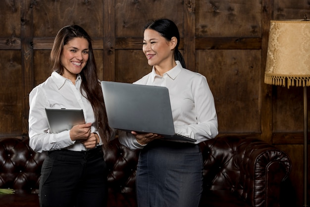 Smiley womens looking at laptop Free Photo