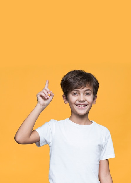 Smiley young boy pointing Free Photo