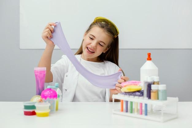 웃는 어린 소녀 과학자 점액 만들기 무료 사진