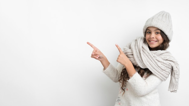 Smiley young girl with hat and scarf pointing Free Photo