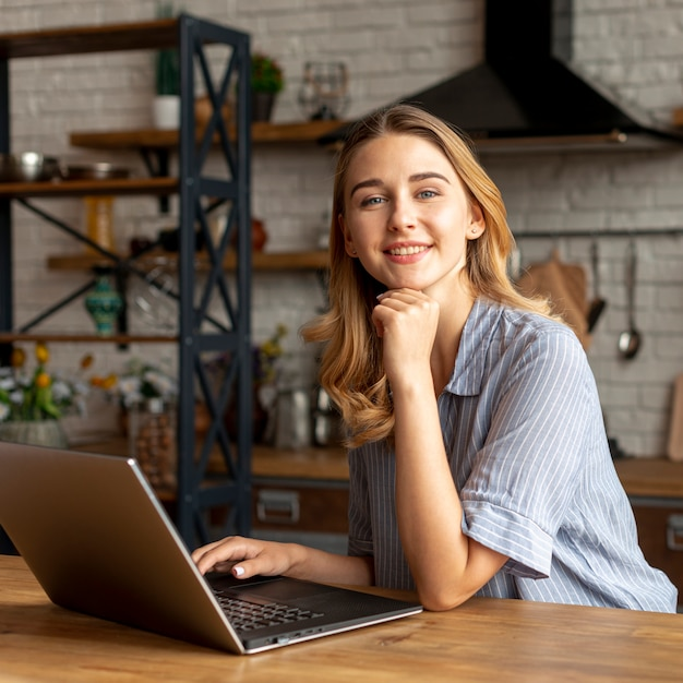 Smiley young girl with a laptop Free Photo