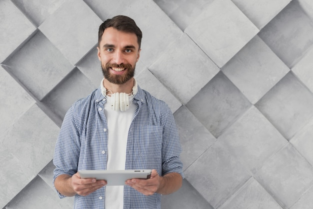 Smiley young man holding tablet mock-up Free Photo
