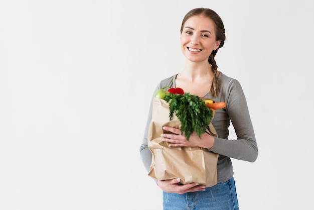 Smiley young woman holding paper bag with groceries Free Photo