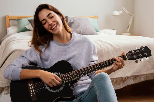 집에서 기타를 연주 웃는 젊은 여자 무료 사진