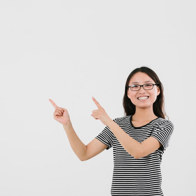 Smiley young woman pointing up with copy space Free Photo