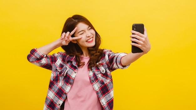 カジュアルな服装で肯定的な表情でスマートフォンで自分撮り写真を作る愛らしいアジアの女性の笑顔と黄色の壁越しにカメラ目線。幸せな愛らしい喜んで女性は成功を喜ぶ。 無料写真