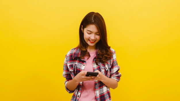 Smiling adorable asian female using phone with positive expression, smiles broadly, dressed in casual clothing and looking at camera over yellow wall. happy adorable glad woman rejoices success. Free Photo