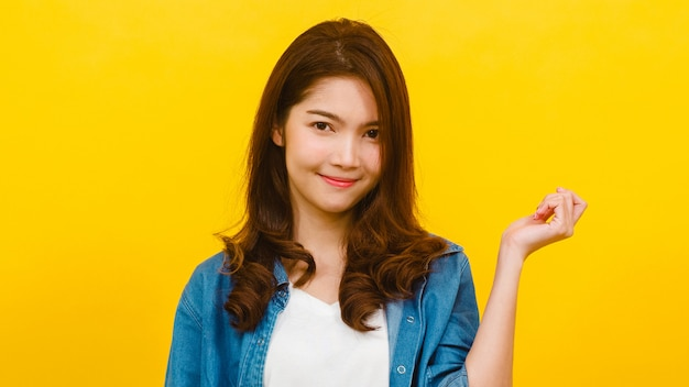 Smiling adorable asian female with positive expression, smiles broadly, dressed in casual clothing and looking at the camera over yellow wall. happy adorable glad woman rejoices success. Free Photo