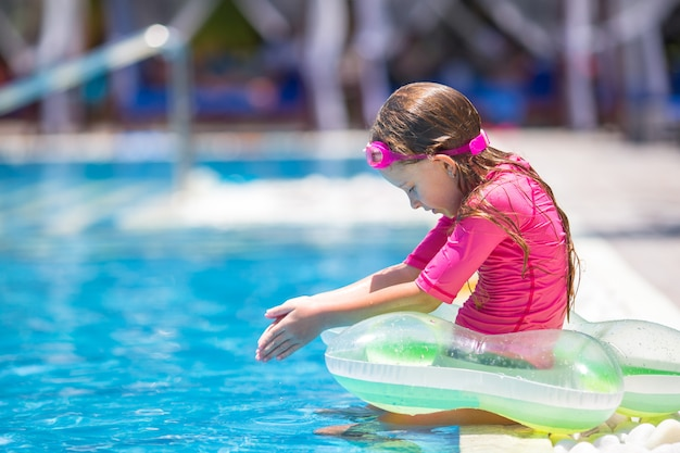 Smiling adorable girl having fun in outdoor swimming pool Premium Photo