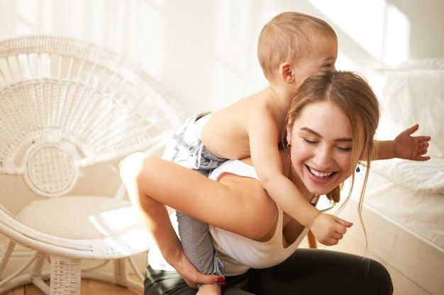 Sorridente adorabile ragazza adolescente baby sitter ragazzino, dandogli un giro sulle spalle a casa. gioiosa giovane madre che cavalca il suo dolce bambino sulla schiena, godendo del bel tempo insieme al chiuso, divertendosi Foto Gratuite