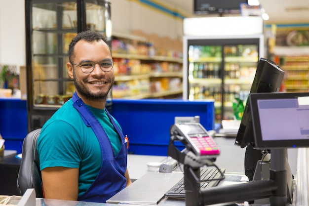 Smiling african american cashier sitting at checkout Free Photo