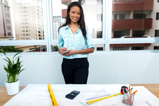 Smiling African-American lady taking notes near plan on table with equipments Free Photo