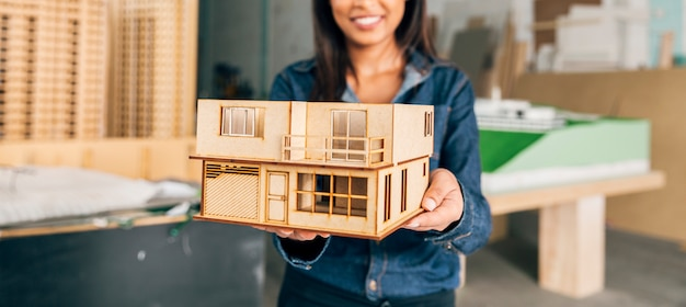 Smiling african american woman showing model of house Free Photo