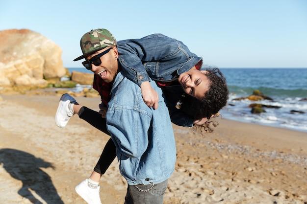 Coppie amorose africane sorridenti che camminano all'aperto alla spiaggia Foto Gratuite