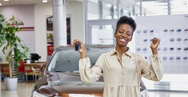 그녀의 새 차에서 키와 웃는 아프리카 여자 프리미엄 사진