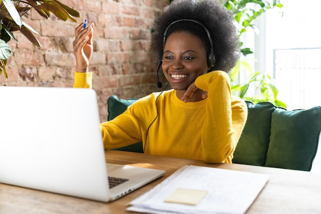 Smiling afro-american woman employee wear headphones, talking on laptop at home office. Premium Photo
