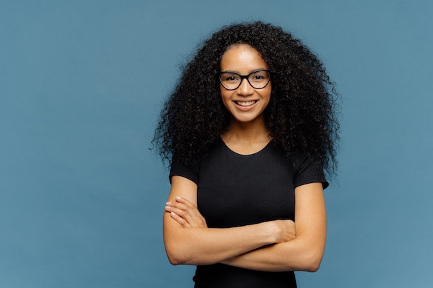 Smiling afro american woman has arms folded, wears spectacles and casual black t shirt Premium Photo