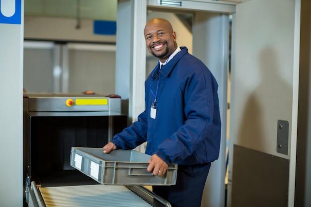 Ufficiale di sicurezza aeroportuale sorridente che tiene una cassa vicino al nastro trasportatore Foto Gratuite