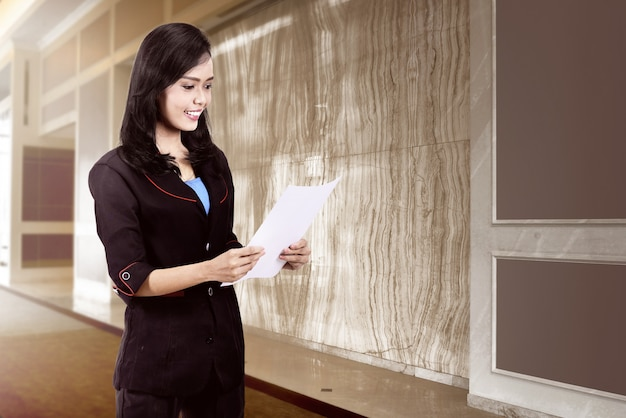 Smiling asian business woman holding a paper Premium Photo