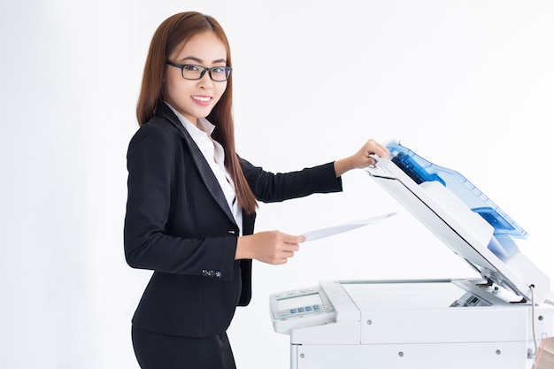 Smiling asian business woman using copier machine Free Photo