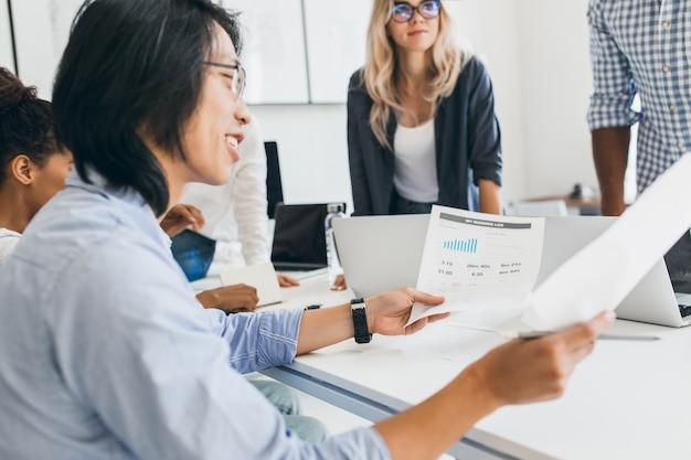 Sorridente uomo d'affari asiatico analizzando infografica nel suo ufficio. ritratto dell'interno di giovani specialisti it con sviluppatore cinese in bicchieri Foto Gratuite