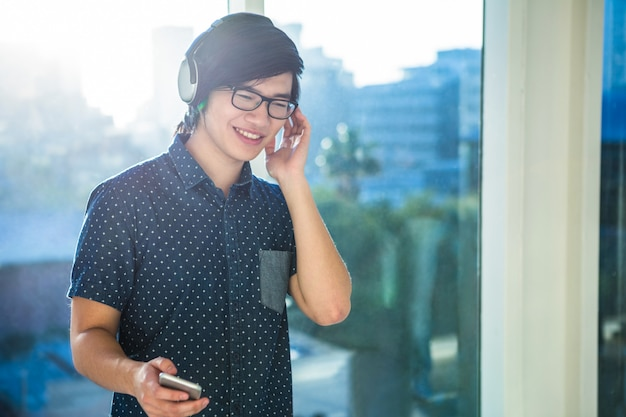 Smiling asian businessman listening to music in office Premium Photo