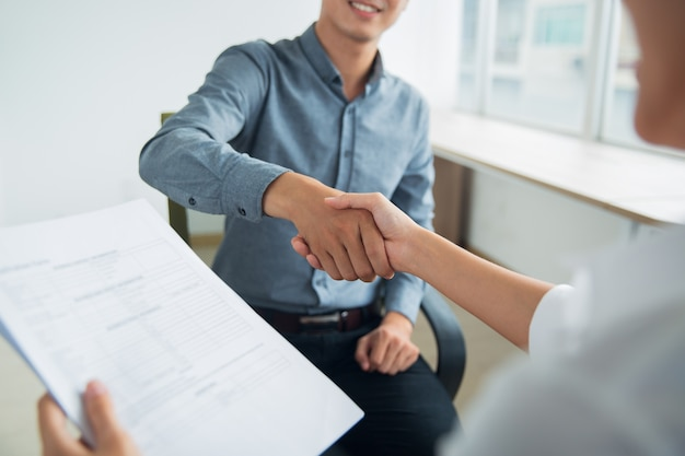 Smiling Asian businessman shaking partners hand Free Photo