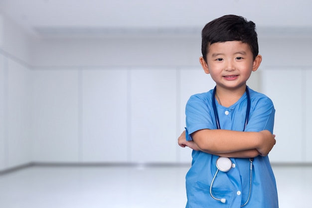 Smiling asian kid in blue medical uniform holding stethoscope Premium Photo