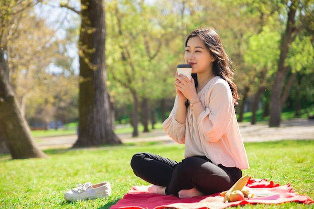 Smiling asian lady drinking coffee and sitting on lawn Free Photo
