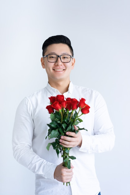 Smiling asian man holding bunch of roses Free Photo