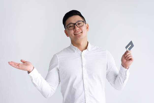 Smiling asian man holding credit card and throwing up hand Free Photo