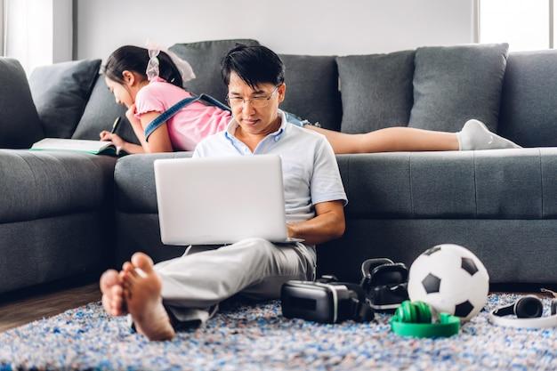 ラップトップコンピューターの作業とテレビ会議のチャットを使用してリラックスできるアジア人の男の笑みを浮かべて本を読んで、ホームコンセプトからhome.workで知識を学ぶ彼の女の子の娘とチャット Premium写真